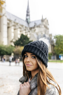 France, Paris, portrait of happy young woman in front of Notre Dame - MGOF02732