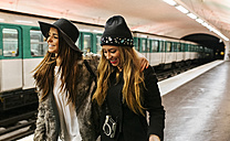 Paris, France, two happy friends at underground station platform - MGO02738