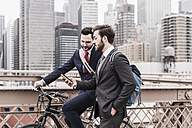 USA, New York City, two businessmen with bicycle and cell phone on Brooklyn Bridge - UUF09638