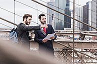 USA, New York City, two businessmen talking on Brooklyn Bridge - UUF09647