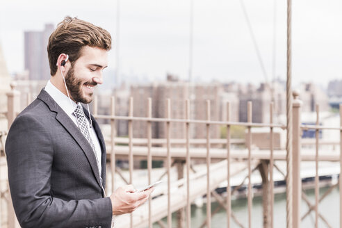 USA, New York City, smiling businessman with cell phone and earbuds on Brooklyn Bridge - UUF09653