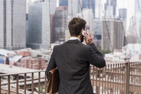 USA, New York City, businessman on Brooklyn Bridge talking on cell phone - UUF09656