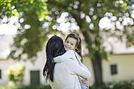 Mother carrying daughter in garden - ZEF12340