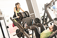 Man exercising in gym lifting woman on weights - JASF01423