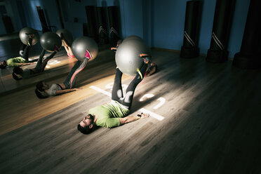 Man and woman exercising with fitness ball in gym - JASF01426
