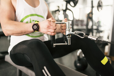 Close-up of man exercising with rowing machine in gym - JASF01435