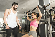Coach training woman in gym - JASF01438