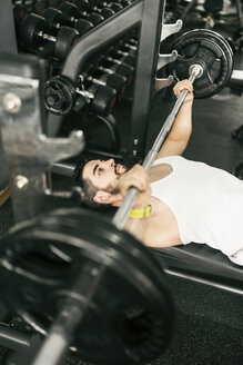 Man training pectoral muscle with bench press in gym - JASF01441