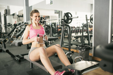 Woman training hard in gym with rowing machine - JASF01444