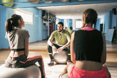 Gym coach explaining exercises to women - JASF01450