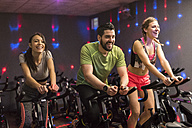 Young people exercising on spinning bikes in gym - JASF01453