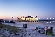 Germany, Usedom, Ahlbeck, view to lighted sea bridge with hooded beach chairs in the foreground at dusk - SIEF07233