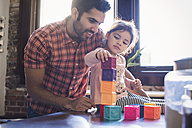 Father and daughter playing with building bricks - WESTF22428