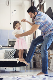 Father balancing his daughter on his foot - WESTF22434