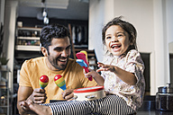 Father and daughter playing music in kitchen - WESTF22440