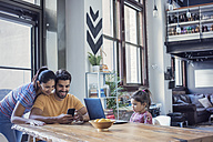 Family sitting in kitchen, parents using smart phone, daughter looking at laptop - WESTF22443