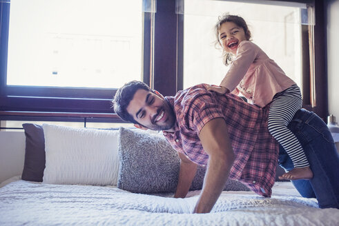 Father and daughter playing on bed - WESTF22455