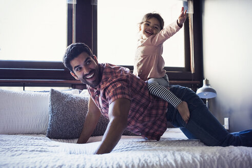 Father and daughter playing on bed - WESTF22458