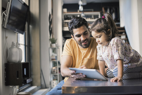 Father and daughter using digital tablet - WESTF22476
