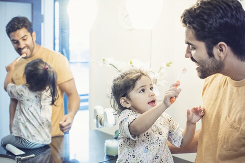 Father and daughter in bathroom brushing teeth - WESTF22488
