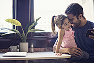 Father with daughter using smart phone in kitchen - WESTF22494