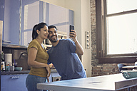 Young couple in kitchen taking selfie - WESTF22506