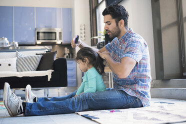 Father sitting on floor doing daughter's hair - WESTF22518