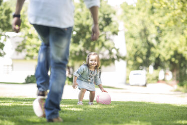 Father playing ball in garden with daughter - ZEF12349