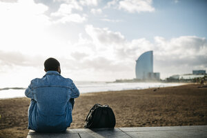 Spain, Barcelona, back view of young traveler sitting at the beach - JRFF01139