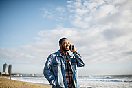 Spain, Barcelona, smiling young man with cell phone on the beach - JRFF01145