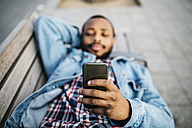 Young man lying on bench looking at cell phone, close-up - JRFF01148