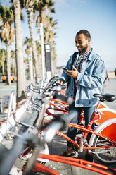 Spain, Barcelona, young man with smartphone renting a city bike - JRFF01154