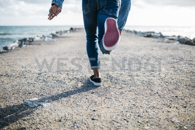 Legs of young man running on jetty - JRFF01157