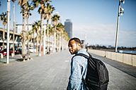 Spain, Barcelona, young man with backpack walking on beach promenade - JRFF01160