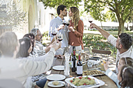 Couple kissing during lunch in garden with red wine - ZEF12368