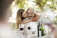 Adult daughter embracing father during lunch in garden - ZEF12371