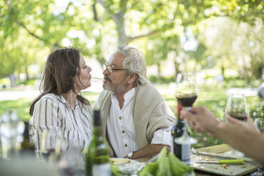 Senior couple sharing spaghetti at outdoor table - ZEF12380