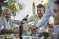 Father and son having wine enjoying family lunch together - ZEF12389