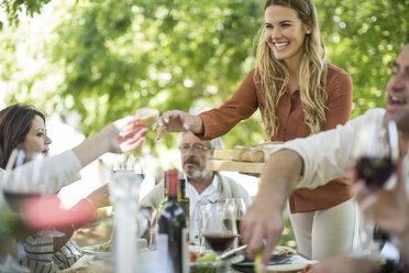 Smiling woman at family lunch in garden - ZEF12395