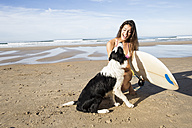 Happy woman with dog and surfboard on the beach - ABZF01713