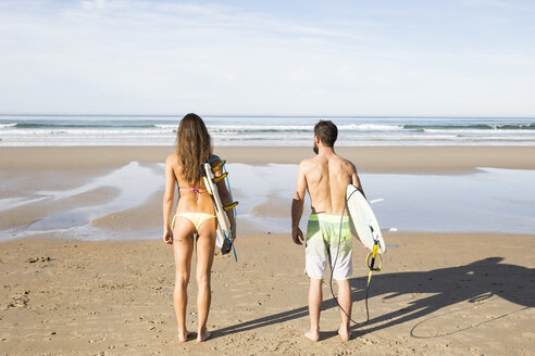 Couple carrying surfboards on the beach - ABZF01716