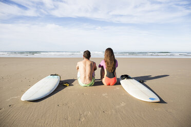 Couple with surfboards sitting on the beach - ABZF01725