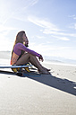Couple with surfboards sitting on the beach - ABZF01728