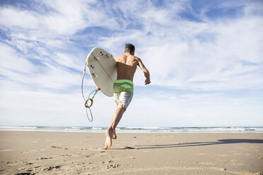 Man carrying surfboard running on the beach - ABZF01731