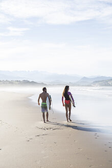 Couple carrying surfboards walking on the beach - ABZF01737