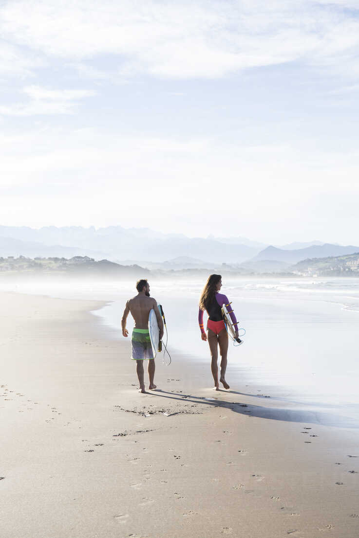 Couple carrying surfboards walking on the beach - ABZF01737 - Andrés Benitez/Westend61