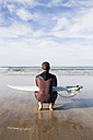 Man with surfboard crouching on the beach - ABZF01740
