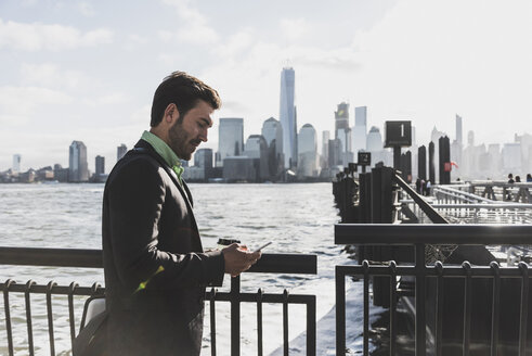 USA, businessman using cell phone at New Jersey waterfront with view to Manhattan - UUF09692