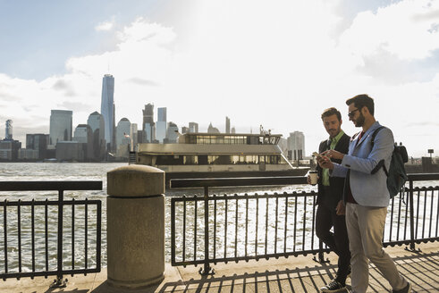 USA, two businessmen walking at New Jersey waterfront with view to Manhattan - UUF09695