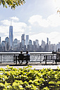 USA, two businessmen sitting on bench at New Jersey waterfront with view to Manhattan - UUF09704
